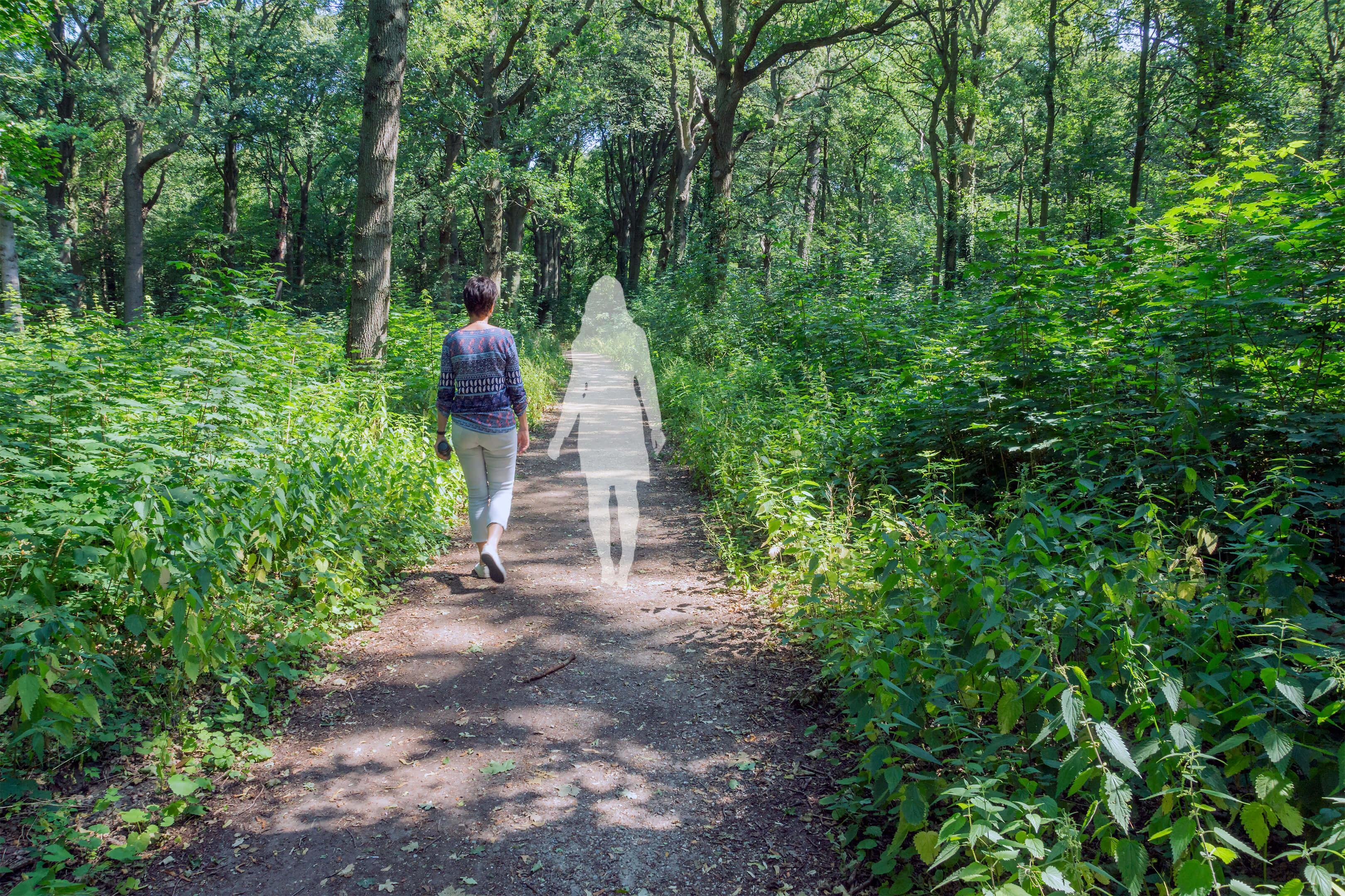 Foto van wandelcoach Claudia van Leent met een denkbeeldige cliënt op een bospad.