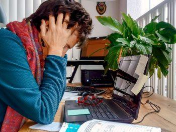 Foto van vrouw achter laptop. De vrouw heeft de handen in het haar. Ze komt er niet meer. Burnout of burn-out verschijnselen?